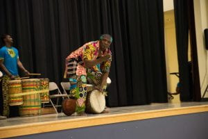 Guinean African master drummer, Alseny Yansane, in traditional clothes, stands smiling over his djembe at the front of a stage. One hand reaches to the drum lying on its side beneath him, the other is outstretched to the crowd.
