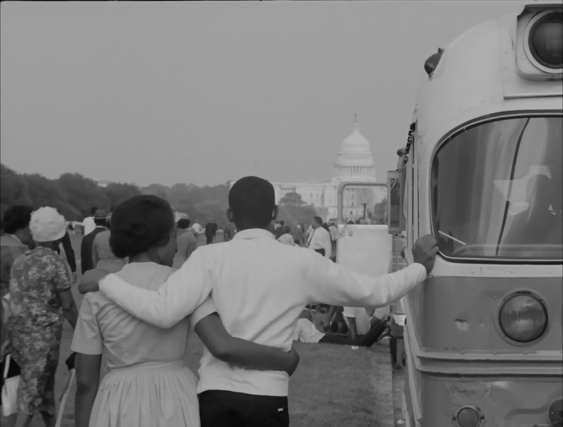 Two people stand arm in arm in front of the US Capitol building.