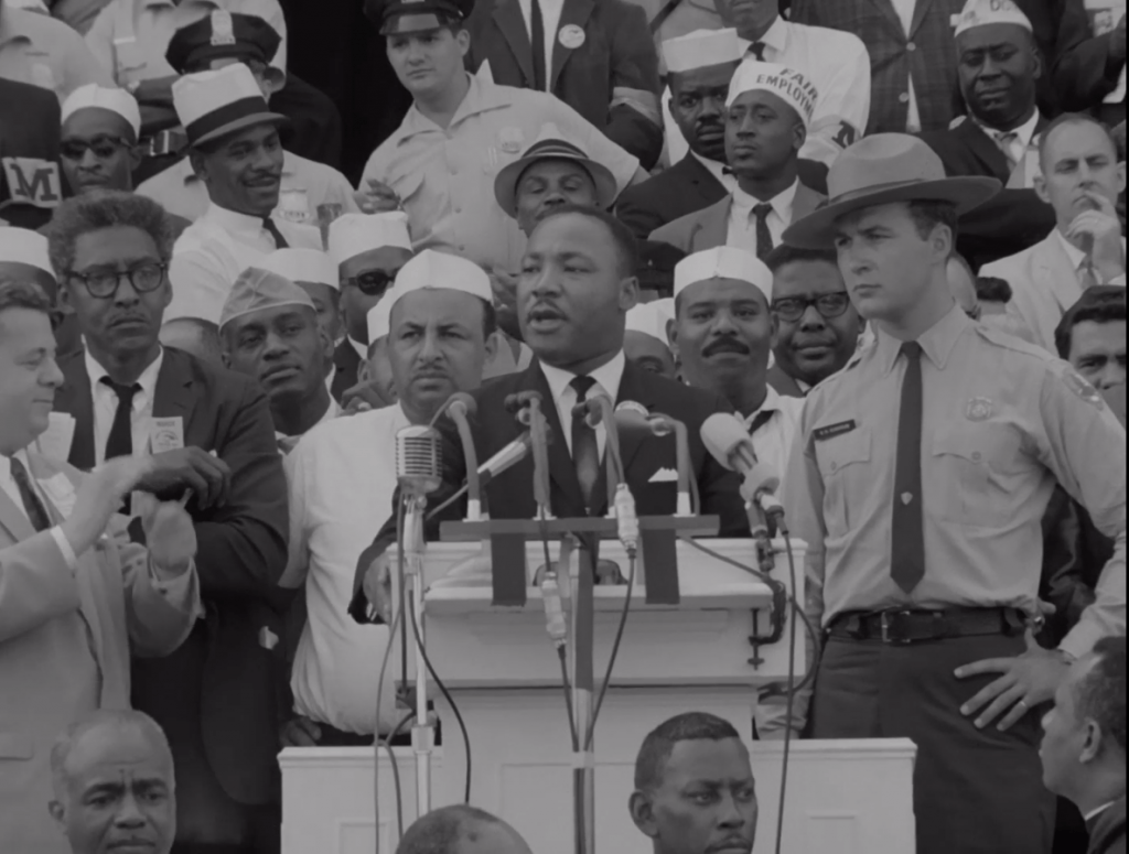 Martin Luther King, Jr., speaks at a podium. On his left is Bayard Rustin, and on his right is a police officer.