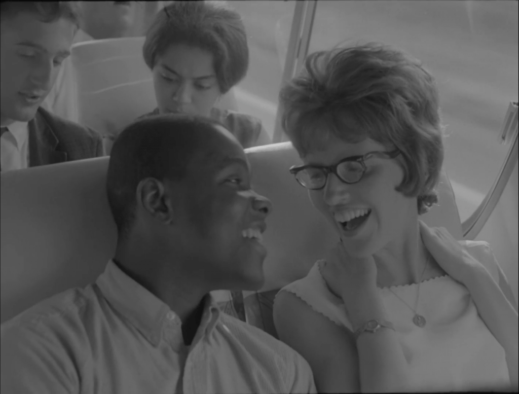 A man and a woman laugh while sitting next to each other on a bus.