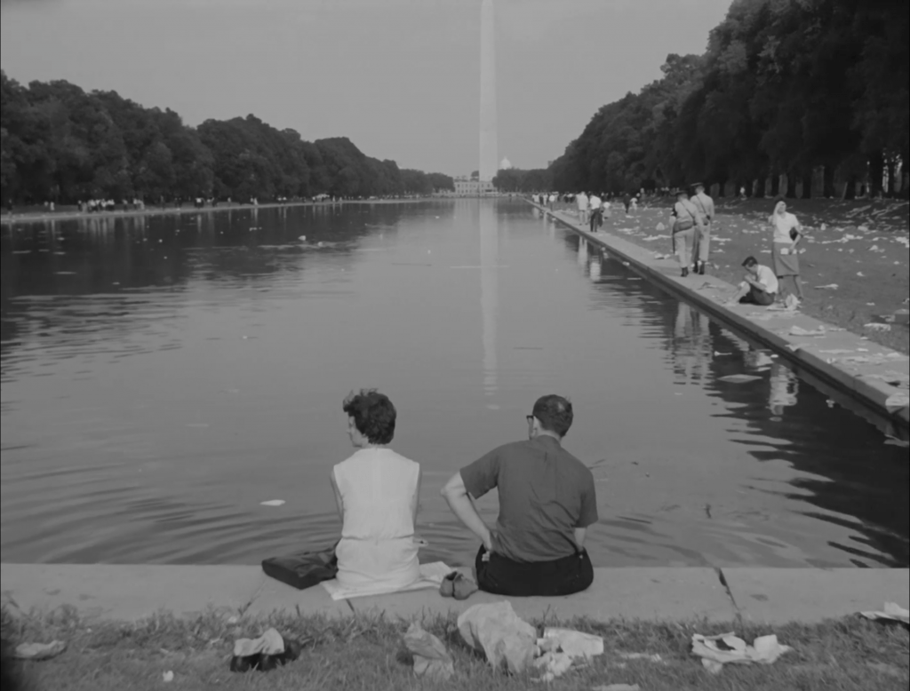 People sit on the edge of the reflecting pool on the National Mall (Washington, DC), facing the Washington Monument. There is litter on the ground left after the March on Washington.