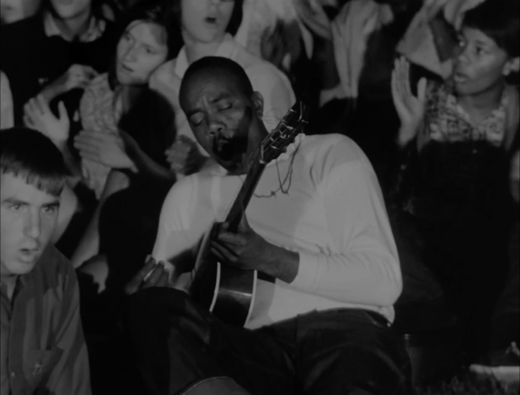 A man plays guitar in a crowd of people singing.