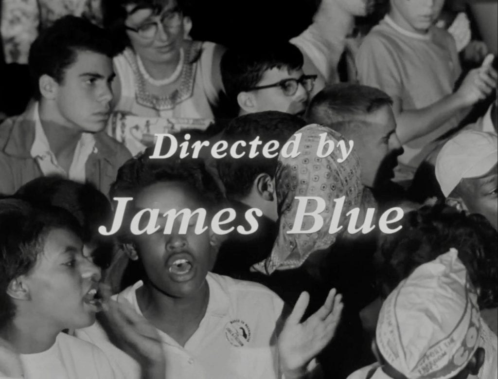 "A film still showing people singing with the title ""Directed by James Blue."""