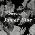 """A film still showing people singing with the title """"Directed by James Blue."""""""