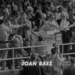 Joan Baez plays guitar at a podium.