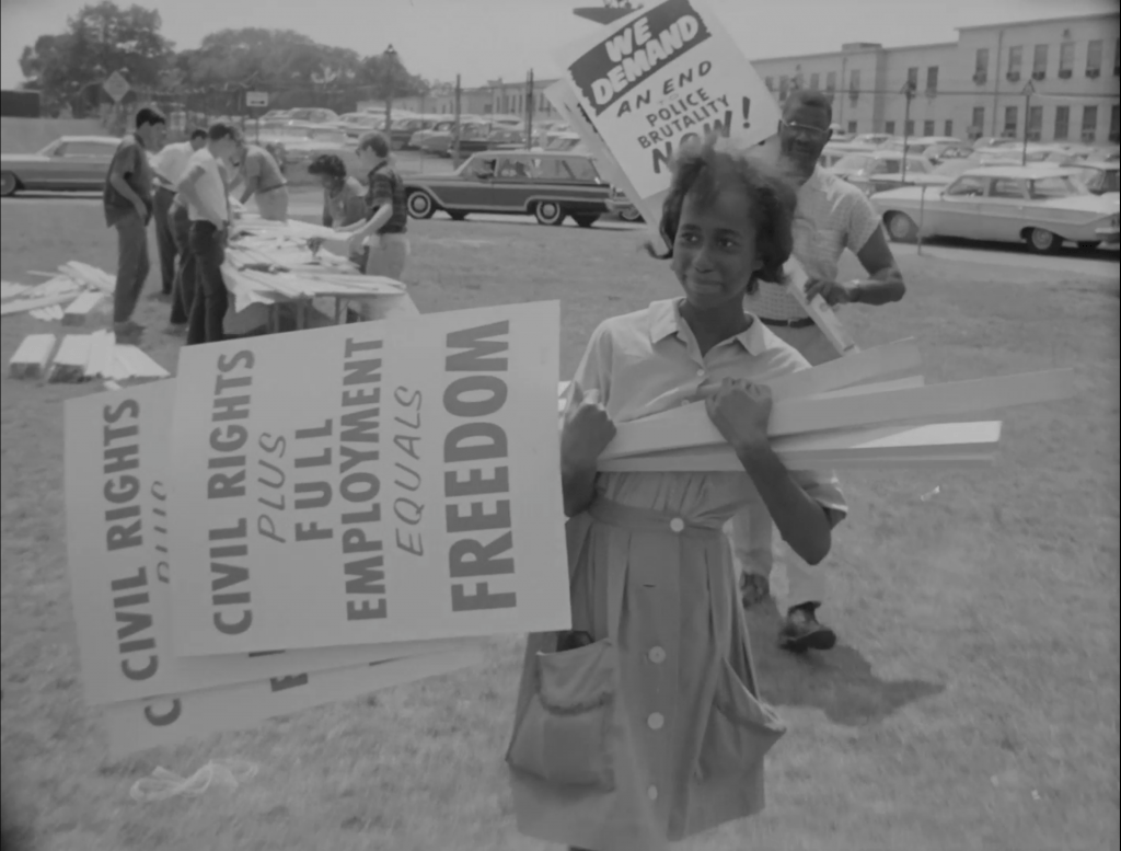 A woman carries protest signs.