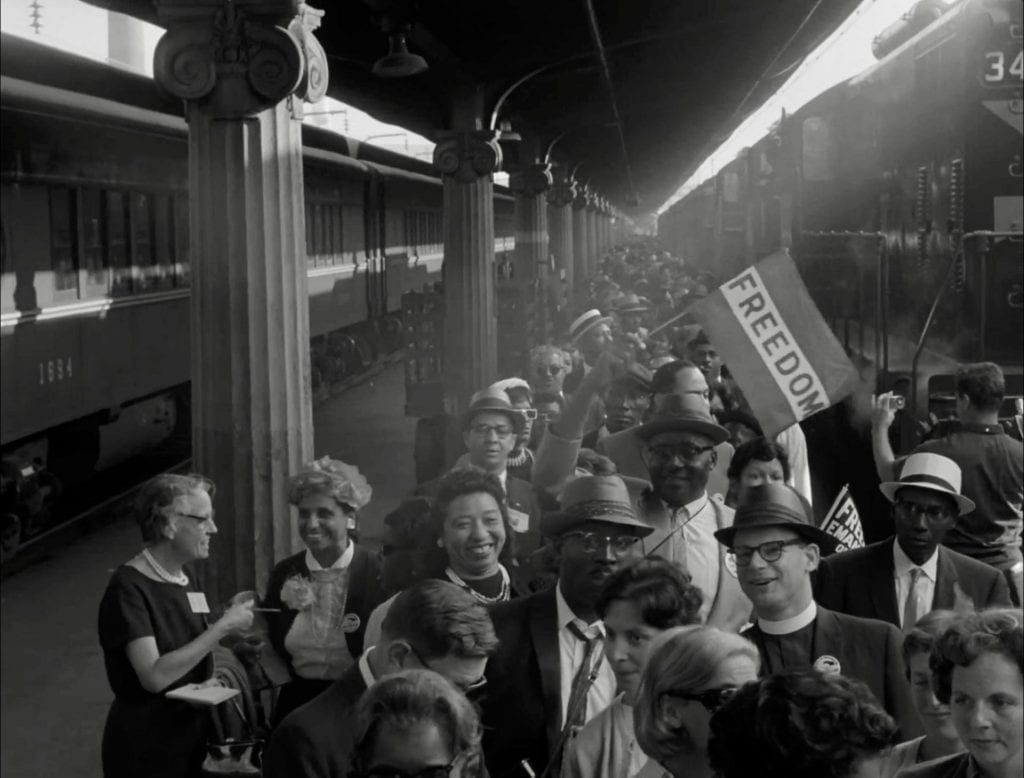 """People walk along a train platform; one waves a banner with the slogan """"Freedom."""""""