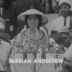 Marian Anderson stands at a podium with several microphones.