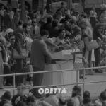 Odetta plays guitar at a podium.