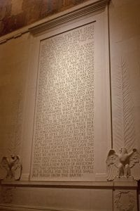 A photo of the text of the Gettysburg Address inscribed on a wall of the Lincoln Memorial, with eagles, wreaths, and palm branches carved in low relief at its sides.