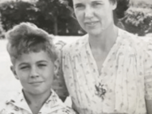 A photograph showing James Blue as a boy standing next to his mother.