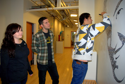 Brad Saiki adds text to the portrait of UO Professor John Park, while collaborators, Zach Yarrington and Lauren Seiffert observe.