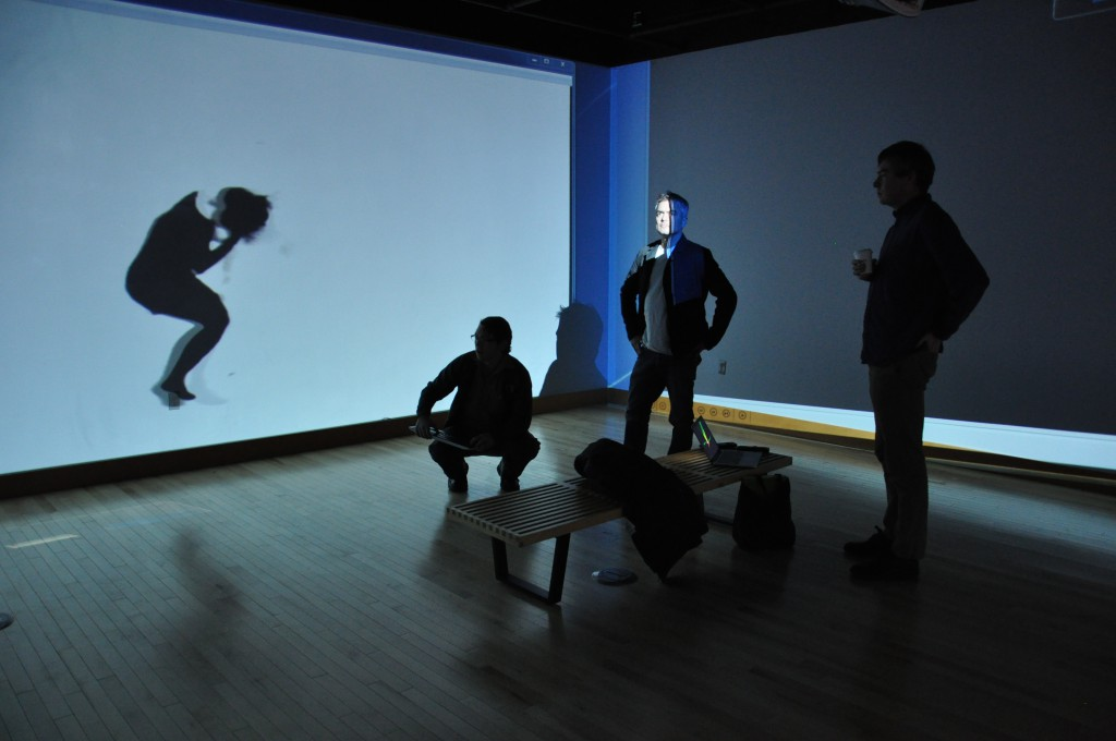 "Cris Moss, center, prepares with UO staff Chris Cosler (left) and artist Carl Diel (right) to set up a video installation in the Gray Box.  Projected on the wall is ""Wrest_01,"" work by artist Heidi Schwegler exhibiting in the Gray Box."