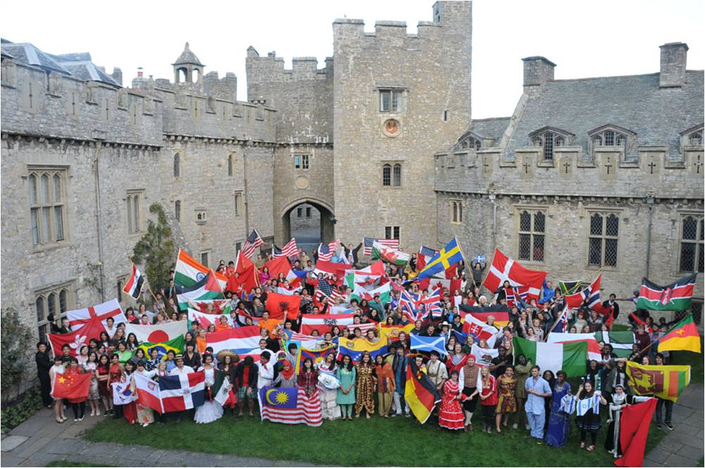 Students at Atlantic College wearing their national costumes and holding their flags in the castle's inner courtyard