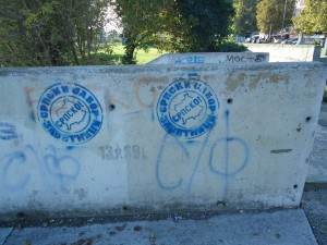 "Graffiti on the bridge in Mitrovica with the country of Kosovo and the word ""Serbian"" stamped on it."