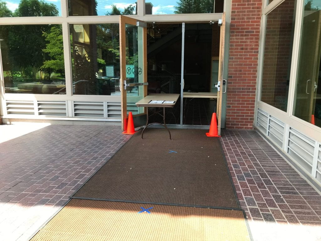 Photograph of the side door to Reid Campus Center, with a long table extending out the door, orange cones marking the doorway, and blue tape marking places to stand in line