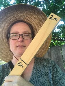 "Photo of Janet wearing a sunhat and holding a tick marked ""6ft"" and ""2m"""