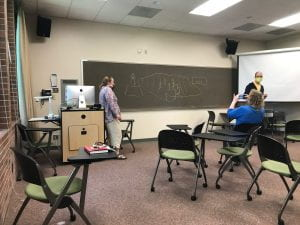 The artist stands by the chalkboard while two others gesture and talk to each other