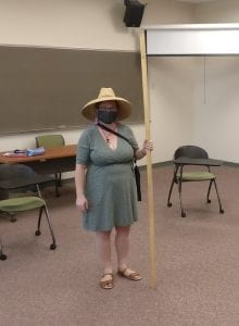 Five-foot tall woman standing in a classroom holding up a 2-meter tall stick