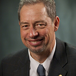 Portrait of Christian Hansen, he has short grey hair and a small beard on his chin. He smiles at the camera, wearing a suit and tie against a grey bakcground.