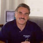 Portrait of N. Douglas Lees. A man with short grey hair and a large mustache smiles, he wears a purple polo shirt while sitting in an office.