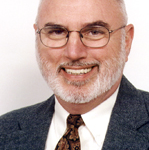 Portrait of Daniel W. Wheeler. A man with with a short white beard smiles, wearing thin framed glasses and a suit and tie against a white background.