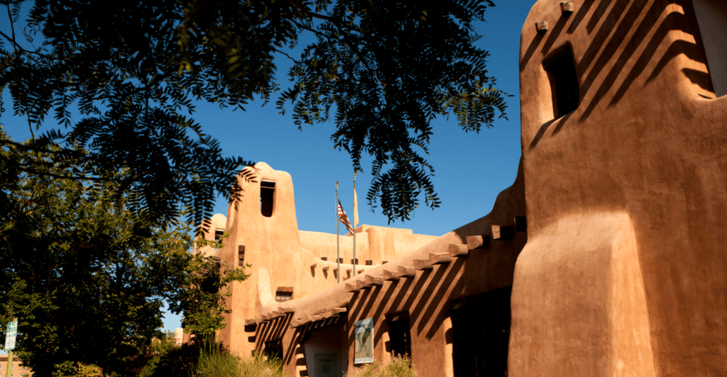 Photo of a pueblo styled building is framed by tree branches