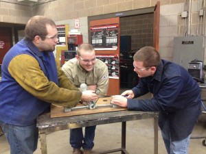 Alumnus Jay O'brien (left) teaches students how to wire an electric circuit.