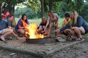 ACT members roast marshmallows for s'mores after a canoeing adventure.