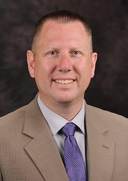 Ulmer posing for headshot in a tan suit jacket and white button up with a purple tie.