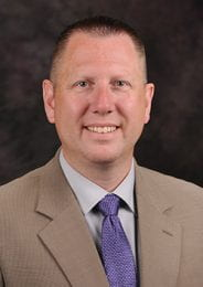 Ulmer is in a tan suit with white button up and purple tie for his headshot