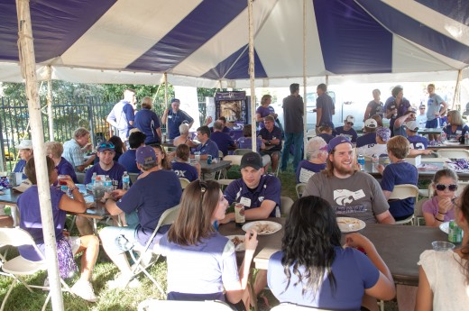 People in purple K-State shirts eating barbecue under a white and purple striped tent.