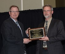 Dr. Peter Dorhout presents Dr. Rollie Clem with K-INBRE mentoring award