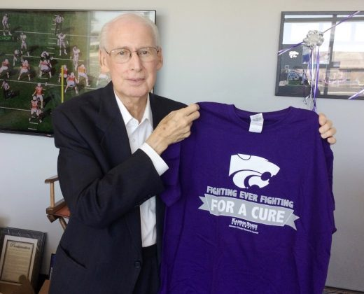 K-State Head Football Coach Bill Snyder holding Fighting for a Cure shirt