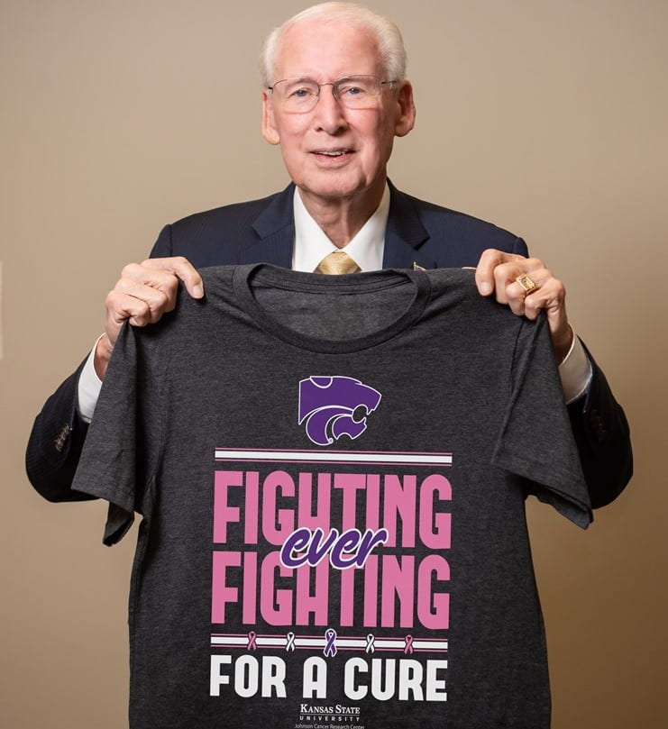 Coach Bill Snyder holding 2019 Fighting for a Cure shirt