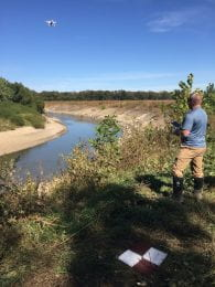 Man stands on a streambank piloting a drone which is taking photos of the Cottonwood River.