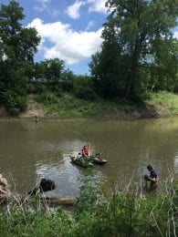 Three people, two on the river bank and one in a boat, take measurements on the Cottonwood River.