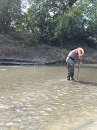Man stands in middle of river with long pole to install scour chains in the water