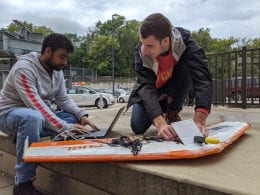 Two male students use a computer and other tools to test a GPS system in a drone.