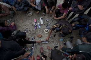 Nepalese villagers charge their cell phones in an open area in Kathmandu, Nepal, Monday, April 27, 2015. Shelter, fuel, food, medicine, power, news, workers — Nepal's earthquake-hit capital was short on everything Monday as its people searched for lost loved ones, sorted through rubble for their belongings and struggled to provide for their families' needs.. (AP Photo/Bernat Armangue)