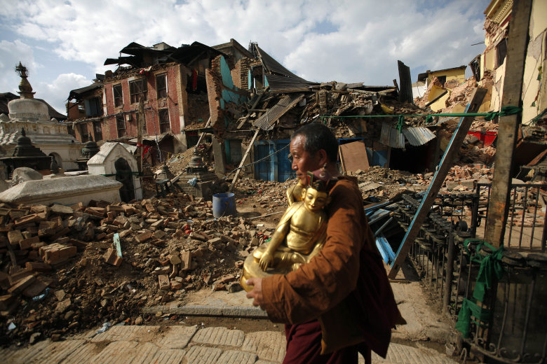 A Buddhist monk salvages a statue of a Buddhist deity from a monastery around the famous Swayambhunath stupa after it was damaged by Saturday's earthquake in  Kathmandu, Nepal, Thursday, April 30, 2015. In mere seconds, Saturday's earthquake devastated a swathe of Nepal. Three of the seven World Heritage sites in the Kathmandu Valley have been severely damaged, including Durbar Square with pagodas and temples dating from the 15th to 18th centuries, according to UNESCO, the United Nations cultural agency. (AP Photo/Niranjan Shrestha)
