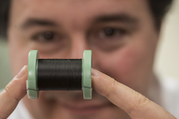 Rice scientist Matteo Pasquali holds a spool of fiber made of pure carbon nanotubes. The fibers are being studied to bridge gaps in the conductivity in damaged heart tissues.