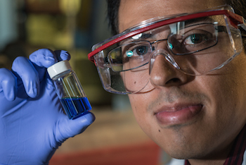 Rice graduate student Victor García-López holds a vial with millions of single-molecule nanosubmersibles.