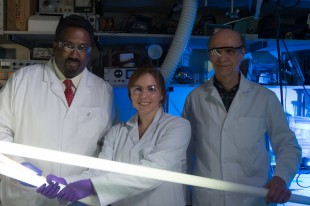 Rice University chemist Paul Cherukuri, left, Texas A&M graduate student Lindsey Bornhoeft, center, and Rice research scientist Carter Kittrell show the power of Teslaphoresis, which wirelessly lights their fluorescent tubes. Tests with a customized Tesla coil revealed that nanotubes within the field self-assemble into wires.