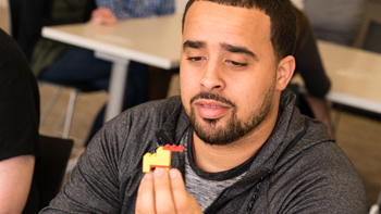 Jerry Lopez, a Web developer at a Houston Internet marketing company, presents a duck he built as part of a Lego Serious Play method workshop facilitated by the Glasscock School.