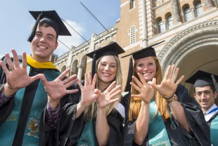 Three graduates make the Owl sign.
