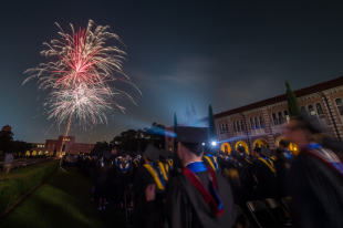 fireworks display with students in commencement robes watching.