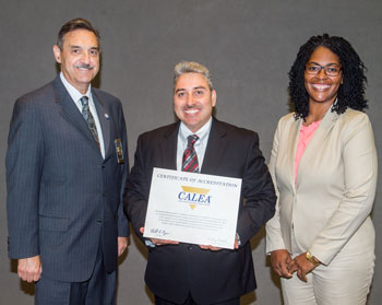 Richard Myers (left), chairman of the Commission on Accreditation for Law Enforcement Agencies Inc., presented RUPD's certificate of accreditation to Capt. Clemente Rodriguez and Sgt. Carla Barnette.