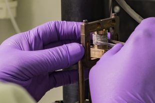 gloved hands placing a sample into a laboratory instrument