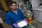 Padmanabha Kattamuri holds a tray of Rice's nitrogen umpolung reagent, which is used as an intermediate in the novel synthesis of secondary amines found in drug candidates and other fine chemicals.